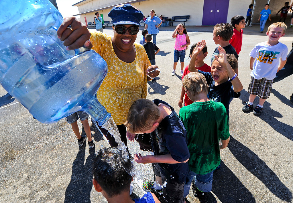 . First grade teacher Nicole Williams pours bottled water on her students at the conclusion of a fun water activity on the final day of school at Hinkley School in Hinkley, Calif. on Thursday, June 6, 2013. Hinkley School is closing for good at the end of the 2012-2013 school year. (Rachel Luna / San Bernardino Sun)