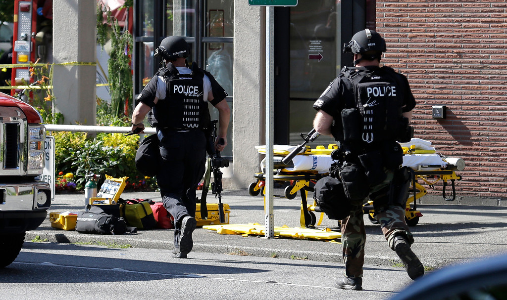 . Seattle Police SWAT officers run toward a campus building following a shooting at Seattle Pacific University on Thursday, June 5, 2014, in Seattle.  A lone gunman armed with a shotgun opened fire Thursday in a building at the small Seattle university, killing one person before he was subdued by a student as he tried to reload, police said. Police say the student building monitor disarmed the gunman and several other students held him until police arrived at the Otto Miller building. (AP Photo/Elaine Thompson)