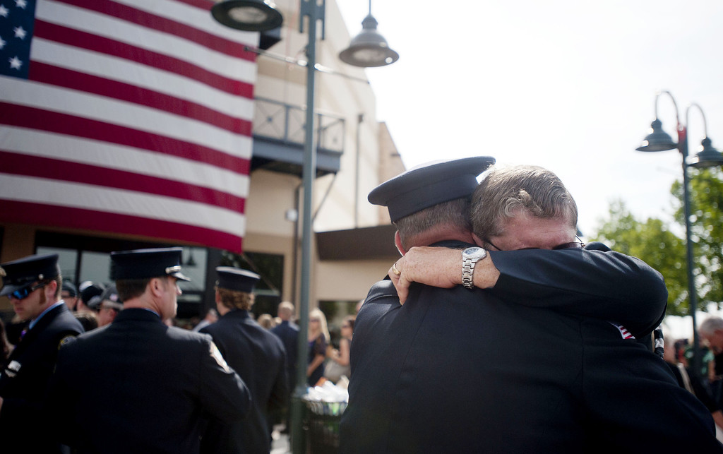. Chaplain Bob Ossler (R) with the Mayer, Arizona fire department hugs people at the entrance to a memorial service honoring the 19 firefighters killed in a wildfire at Tim\'s Toyota Center July 9, 2013 in Prescott Valley, Arizona. T(Photo by Laura Segall/Getty Images)