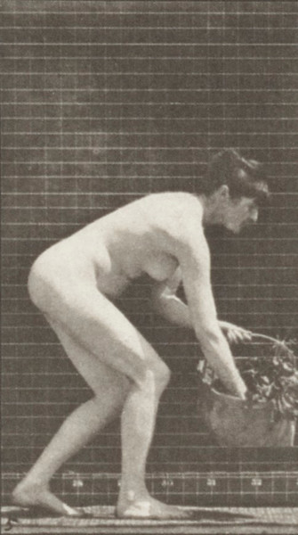 Nude woman lifting and emptying a basket