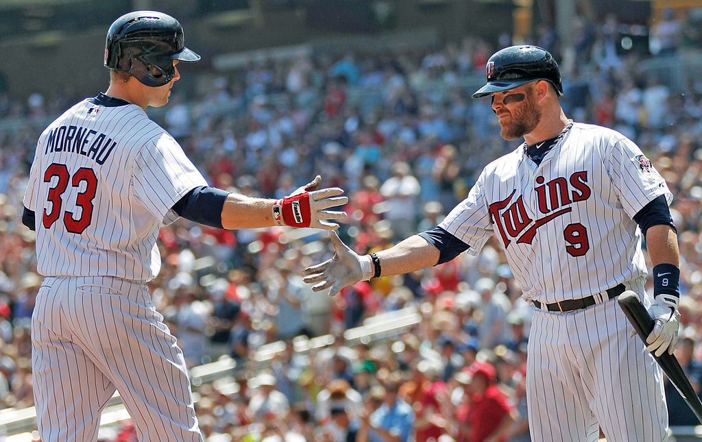 . Minnesota\'s Justin Morneau, left, is congratulated by teammate Ryan Doumit after Morneau\'s solo shot against Royals starter James Shields in the third inning.    (AP Photo/Andy Clayton-King)