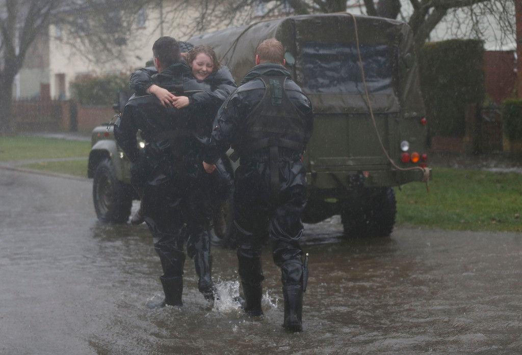 . A soldier from the Royal Engineer carries a young evacuee resident onto dry land through a flooded road  at Egham, England, Wednesday, Feb. 12, 2014.  (AP Photo/Sang Tan)