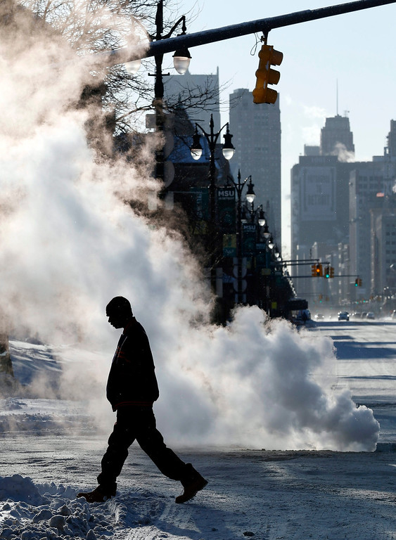 . A man crosses Woodward Avenue in front of a steam vent in Detroit, Michigan, USA, 07 January 2014. A deep freeze threatened much of the eastern US seaboard on 07 January as the mercury plunged into lows not seen in nearly two decades, government forecasters said. \'Dangerously cold Arctic air\' will be descend on the eastern two-thirds of the nation after gripping northern and mid-western states since 05 January, the National Weather Service warned.  EPA/JEFF KOWALSKY