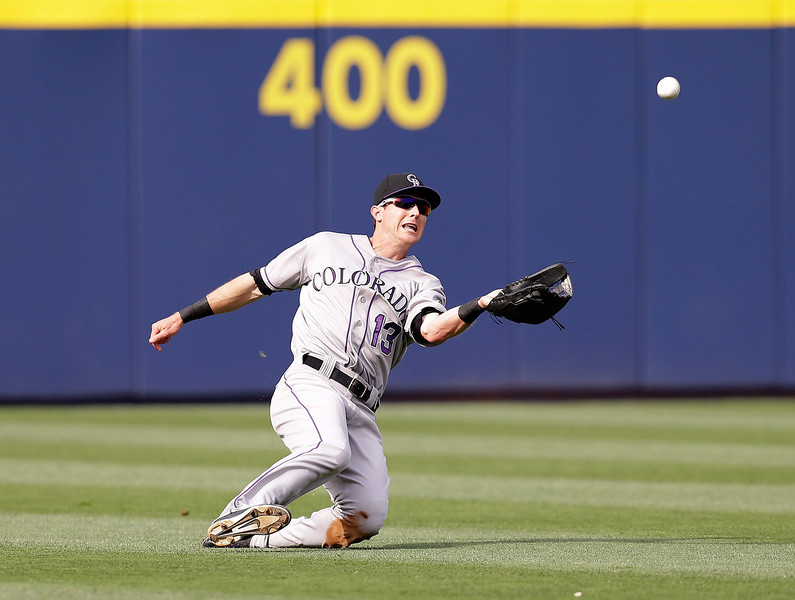 . Centerfielder Drew Stubbs #13 of the Colorado Rockies makes a diving catch in the fifth inning of the game against the Atlanta Braves at Turner Field on May 24, 2014 in Atlanta, Georgia.  (Photo by Mike Zarrilli/Getty Images)