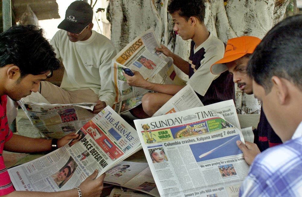 . Indians read newspapers carrying the news of the space shuttle Columbia disaster at a roadside library, in Bombay, India, Sunday, Feb. 2, 2003. Celebrations turned into mourning for relatives and friends of Kalpana Chawla, the first Indian-born woman in space, as the shuttle broke apart shortly before landing in the U.S., killing all the seven astronauts including Chawla. (AP Photo/ Rajesh Nirgude)