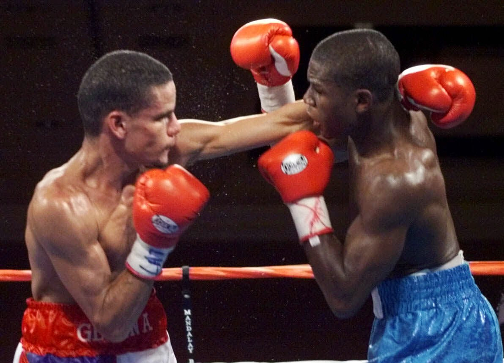 . Carlos Gerena, left,  of Puerto Rico mixes it up with Floyd Mayweather Jr. of Grand Rapids, Mich., during the WBC super featherweight title fight Saturday, Sept. 11, 1999, in Las Vegas. Mayweather retained his title when referee Richard Steele, on advice of a ringside physician, stopped the fight after the seventh round. (AP Photo/Lori Cain)