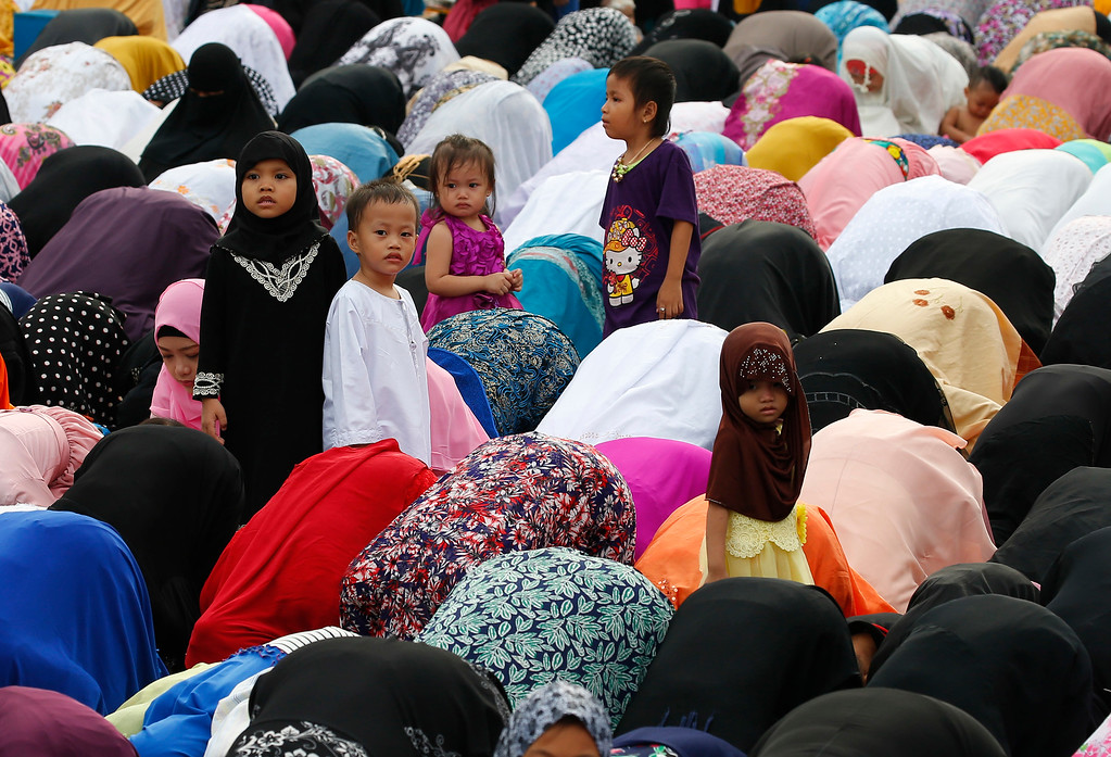 . Children stand amidst Filipino Muslims praying to celebrate the end of the holy month of Ramadan known as Eid al-Fitr Friday, June 15, 2018 at the Blue Mosque in suburban Taguig city, east of Manila, Philippines. Muslims all over the world mark Eid al-Fitr with prayers, family reunions and gift-givings. (AP Photo/Bullit Marquez)