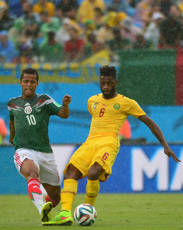 . Mexico\'s forward Giovani Dos Santos (L) challenges Cameroon\'s midfielder Alexandre Song during the Group A football match between Mexico and Cameroon at the Dunas Arena in Natal during the 2014 FIFA World Cup on June 13, 2014.  AFP PHOTO / YURI CORTEZ/AFP/Getty Images
