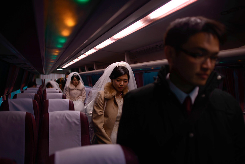 ". Couples disembark from a bus as they arrive for a mass wedding at an event held by the Unification Church in Gapyeong on February 12, 2014. Unification Church members forming 2500 couples from 52 countries were married in a mass wedding in South Korea -- only the second such event since the death of their ""messiah\"" and controversial church founder Sun Myung Moon. (ED JONES/AFP/Getty Images)"