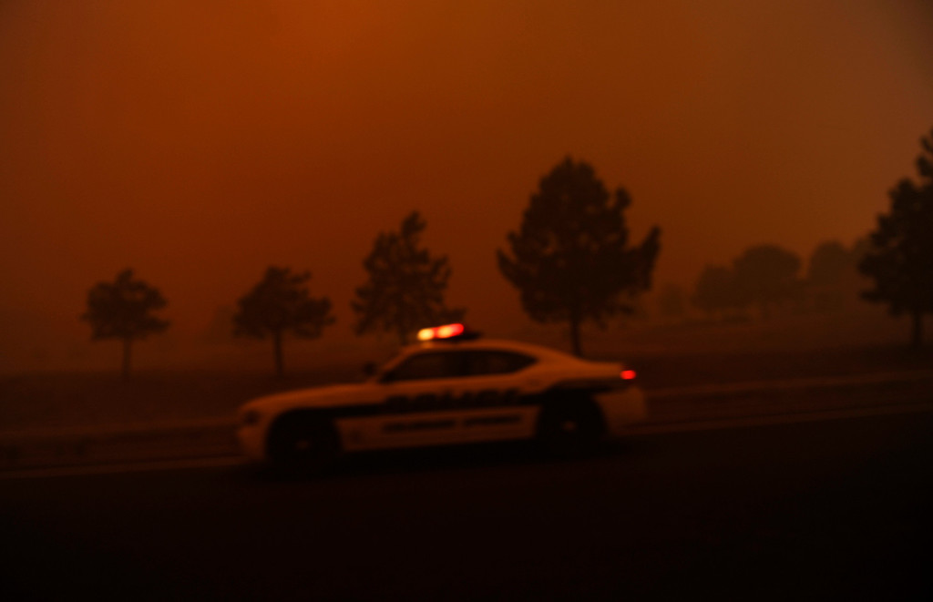 . A Colorado Springs Police Officer rushes to get residents out of their homes in the path of the Waldo Canyon Fire, Tuesday, June 26, 2012. RJ Sangosti, The Denver Post