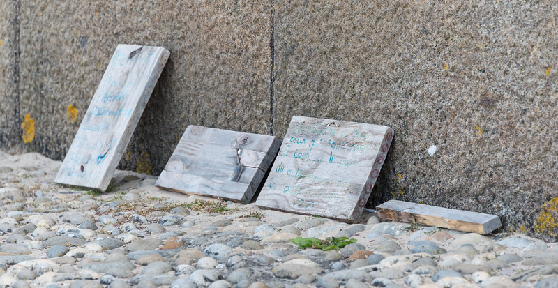At the monument base, personal tributes on driftwood