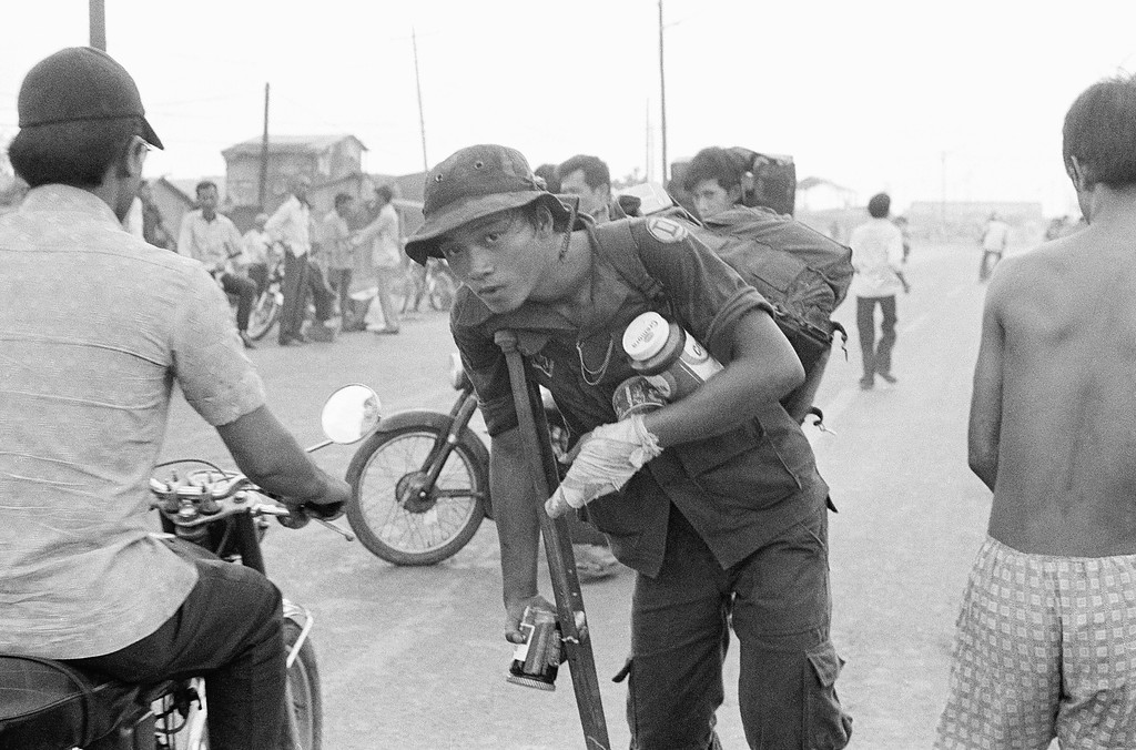 . A crippled South Vietnamese war veteran limps away on crutch with food looted from abandoned U.S. installations after evacuation of Saigon, April 29, 1975. (AP Photo)