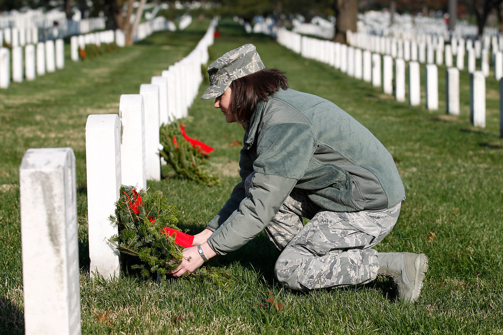 . Airman Lt. Amanda Elliot lays  holiday wreaths over the graves of fallen soldiers during Wreaths Across America Day at Arlington Cemetery on Saturday Dec. 10, 2011.(AP Photo/Jose Luis Magana)