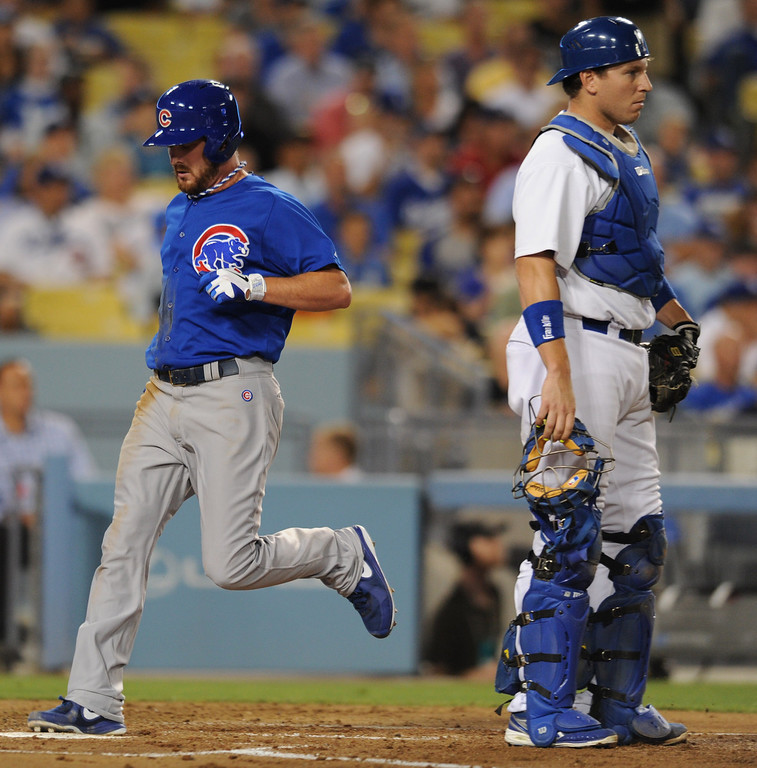 . The Cubs Travis Wood scores, running past Dodger catcher A.J. Ellis at home plate on a DionerNavarro single in the 3rd inning. The Cubs were in town to play the Dodgers. Los Angeles, CA. 8/24/2013(John McCoy/LA Daily News)