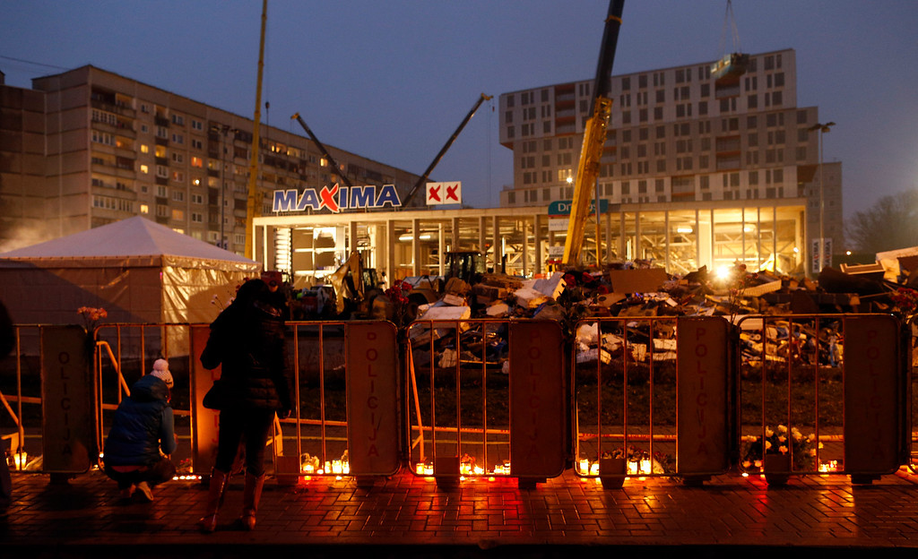 . People lay flowers and light candles in front of the Maxima supermarket in Riga, Friday, Nov. 22, 2013. Hordes of shoppers were picking up food after work in the Latvian capital when an enormous section of the supermarket\'s roof caved in.  (AP Photo/Mindaugas Kulbis)