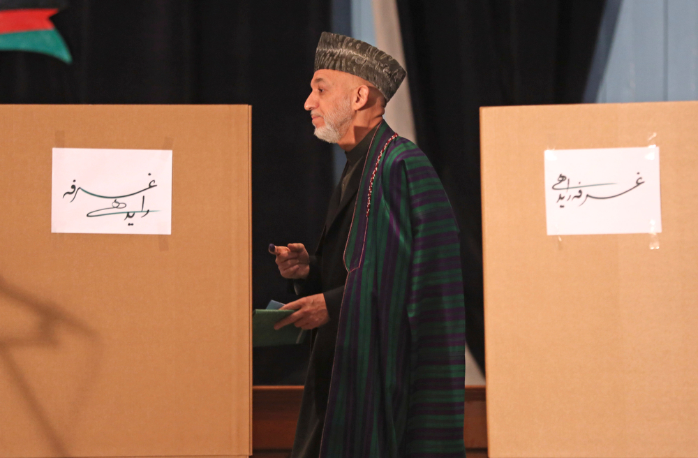 . Afghan President Hamid Karzai, center, walks to the ballot boxes before he casts his vote at Amani high school, near the presidential palace in Kabul, Afghanistan, Saturday, April 5, 2014. Afghan voters lined up for blocks at polling stations nationwide on Saturday, defying a threat of violence by the Taliban to cast ballots in what promises to be the nation\'s first democratic transfer of power. (AP Photo/Massoud Hossaini)