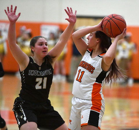 2/14/2020 Mike Orazzi | StaffrTerryville High School's Kassandra McCarthy r(11) and Thomaston's Emily Root (21) during Friday evening's girls basketball game in Terryville.