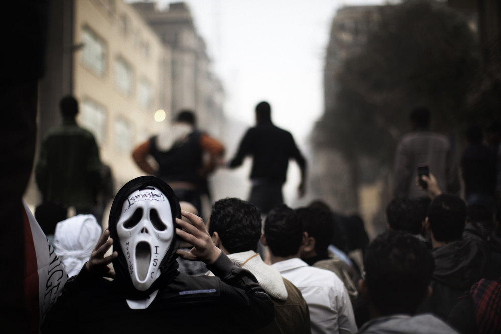 ". An Egyptian demonstrator wears a ""Scary Movie\"" mask as he challenges riot policemen during confrontations in Cairo on February 6, 2012, as protesters and police clashed again outside Cairo\'s security headquarters in the wake of deadly football violence and amid calls by activists for civil disobedience in Egypt.    MARCO LONGARI/AFP/Getty Images"
