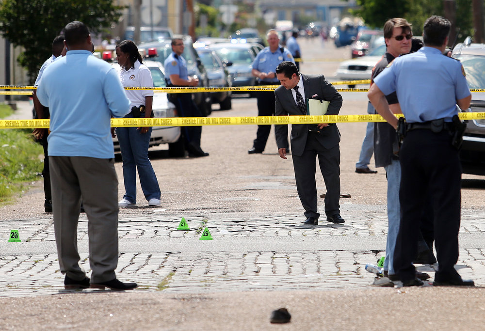 . New Orleans police officers investigate the scene at the intersection of Frenchmen and N. Villere Streets in New Orleans after gunfire at a Mother\'s Day second-line parade on Sunday, May 12, 2013. Police spokeswoman Remi Braden said in an email that many of the 17 victims were grazed and most of the wounds weren\'t life-threatening. No deaths were reported. (AP Photo/The Times-Picayune, Michael DeMocker)