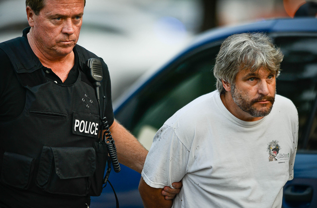 . A person was handcuffed and escorted from the scene where the shooting suspect, Brian Fitch Sr., was apprehended moments before near Rice Street and Sycamore Street in St. Paul on Wednesday. (Pioneer Press: Ben Garvin)