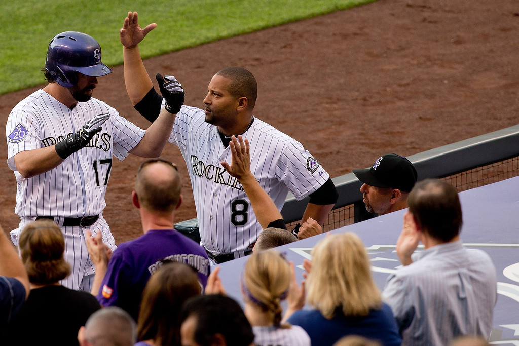 . Todd Helton #17 of the Colorado Rockies celebrates at the top of the dugout with teammate Yorvit Torrealba #8 after hitting a solo home run during the second inning against the Miami Marlins at Coors Field on July 23, 2013 in Denver, Colorado.  (Photo by Justin Edmonds/Getty Images)