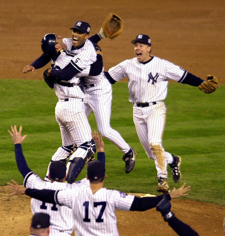 . In this Oct. 27, 1999 file photo, New York Yankees catcher Jorge Posada, left rear, and third baseman Scott Brosius, right rear, rush pitcher Mariano Rivera as teammates run to the mound after the Yankees beat the Atlanta Braves 4-1 in Game 4 of the World Series to sweep the series, in New York.  (AP Photo/Ron Frehm, File)