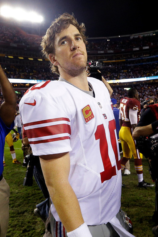 . New York Giants quarterback Eli Manning looks over his shoulder as he leaves the field after an NFL football game against the Washington Redskins in Landover, Md., Monday, Dec. 3, 2012. The Redskins won 17-16. (AP Photo/Patrick Semansky)