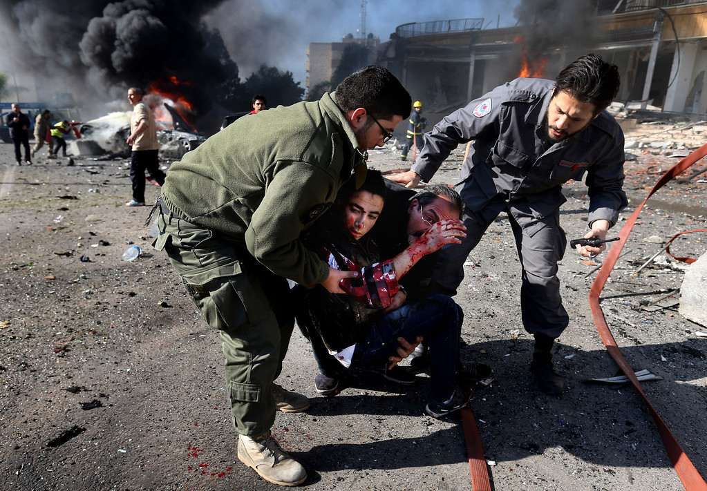. Lebanese civil defense workers carry an wounded man away from the site of an explosion, near the Kuwaiti Embassy and Iran\'s cultural center, in the suburb of Beir Hassan, Beirut, Lebanon, Wednesday, Feb. 19, 2014.  (AP Photo/Hussein Malla)