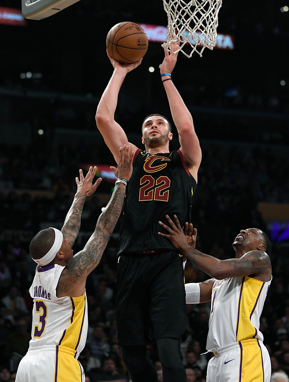 . Cleveland Cavaliers forward Larry Nance Jr., center, shoots as Los Angeles Lakers guard Isaiah Thomas, left, and guard Kentavious Caldwell-Pope defend during the first half of an NBA basketball game, Sunday, March 11, 2018, in Los Angeles. (AP Photo/Mark J. Terrill)
