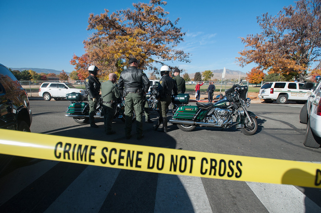 . Police secure the scene near Sparks Middle School after a shooting in Sparks, Nev., on Monday, Oct. 21, 2013.   (AP Photo/Kevin Clifford)