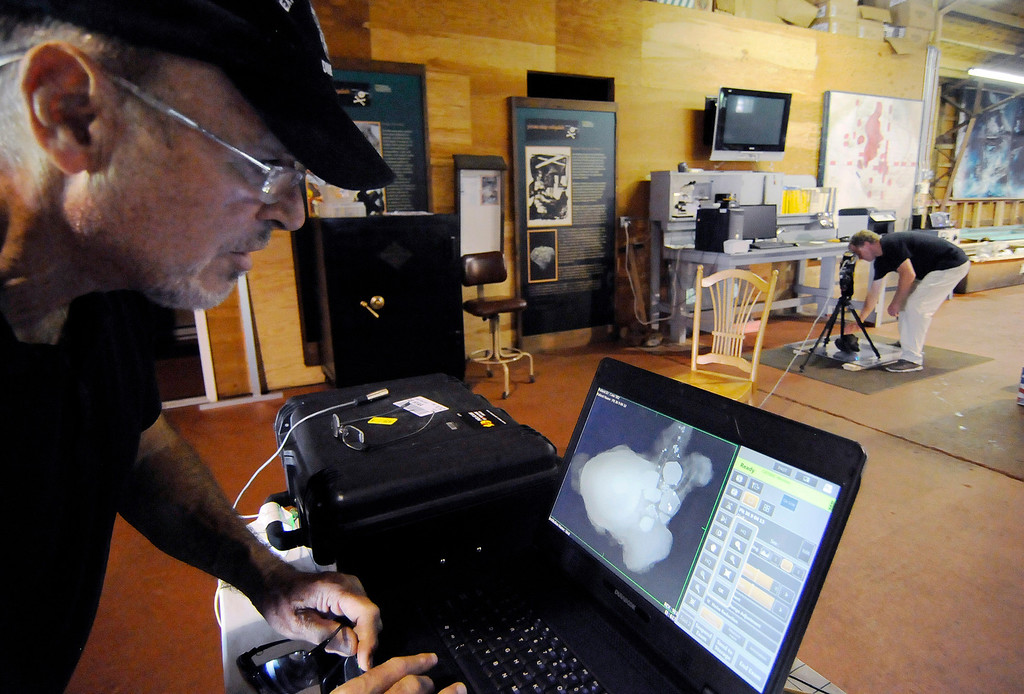 . In this Sept. 4, 2013 photo, explorer Barry Clifford, left, reviews an X-ray image of a concretion showing a cannon ball and coins that diver and conservator Chris Macort, right, had recorded in Brewster, Mass. The concretion is some of the new treasure recovered around the wreck of the Whydah, a pirate ship that sank during a ferocious storm off Cape Cod in 1717. Clifford located the Whydah site in 1984 and has since documented 200,000 artifacts. He only recently got indications there may be far more coins than the roughly 12,000 he\'s already documented. (AP Photo/Cape Cod Times, Merrily Cassidy)