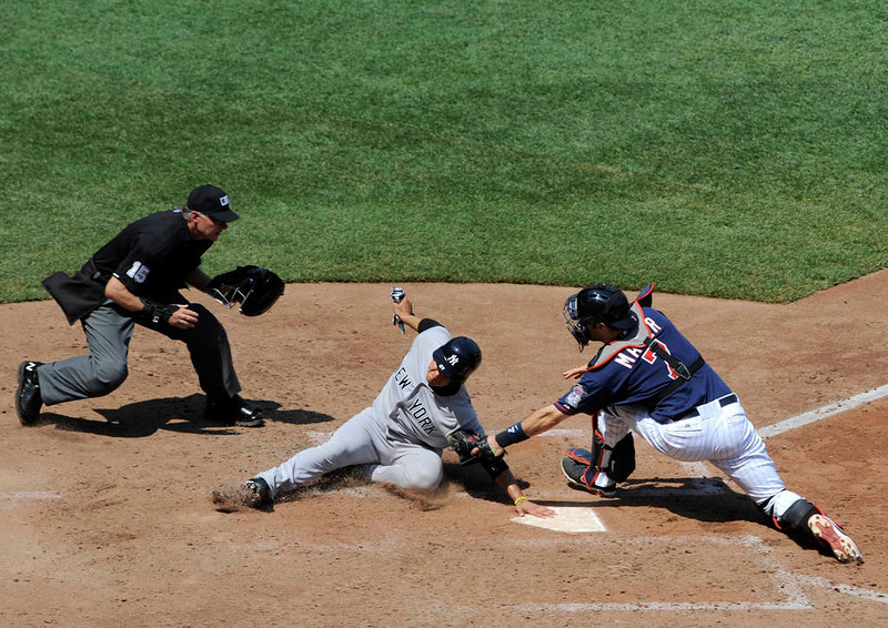 . New York\'s Luis Cruz, center, is tagged out at home by Minnesota catcher Joe Mauer, right, as umpire Ed Hickox looks on during the sixth inning. (Hannah Foslien/Getty Images)