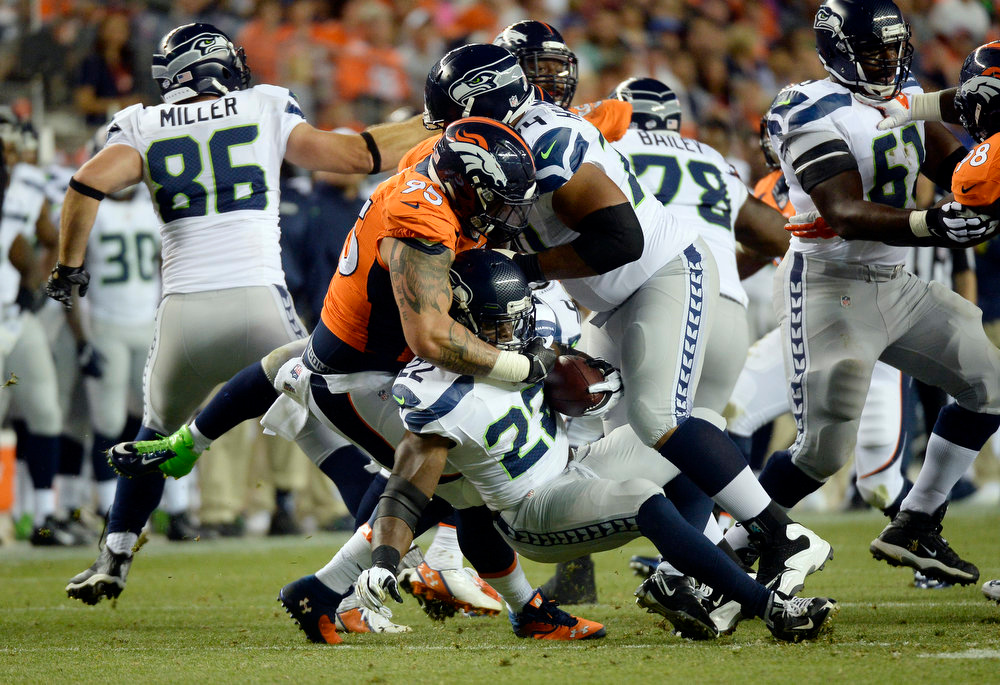 . Running back Robert Turbin (22) of the Seattle Seahawks gets tackled by defensive end Derek Wolfe (95) of the Denver Broncos during the first half of play.  The Denver Broncos vs the Seattle Seahawks At Sports Authority Field at Mile High. (Photo by John Leyba/The Denver Post)