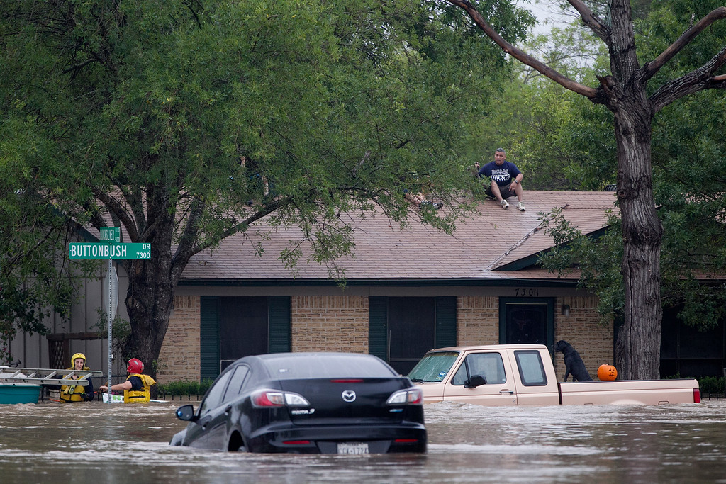 . A man sits on top of a home on Buttonbush Drive in southeast Austin, Texas, on Thursday, Oct. 31, 201 Heavy overnight rains brought flooding to the area. The National Weather Service said more than a foot of rain fell in Central Texas, including up to 14 inches in Wimberley, since rainstorms began Wednesday.  (AP Photo/The Austin American-Statesman, Deborah Cannon)