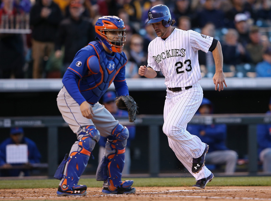. Charlie Culberson #23 of the Colorado Rockies scores behind catcher Travis d\'Arnaud #15 of the New York Mets on a two RBI single by Juan Nicasio #12 of the Colorado Rockies to take a 3-0 lead over the New York Mets in the second inning at Coors Field on May 1, 2014 in Denver, Colorado.  (Photo by Doug Pensinger/Getty Images)