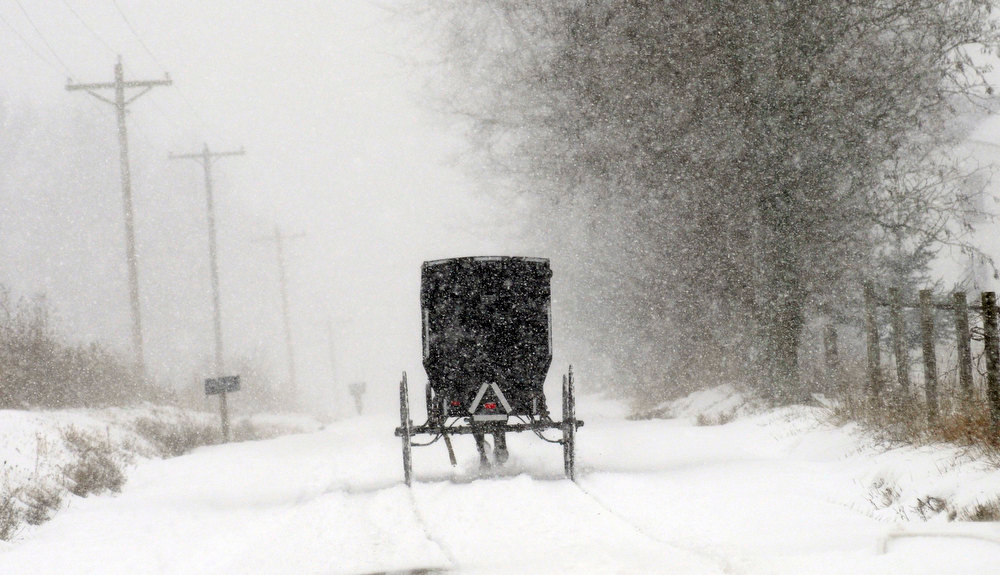 . An Amish buggy makes its way south on Township Road 1353 in Ashland, Ohio during a snow storm Wednesday, Dec. 26, 2012. (AP Photo/Ashland Times-Gazette, Tom E. Puskar)
