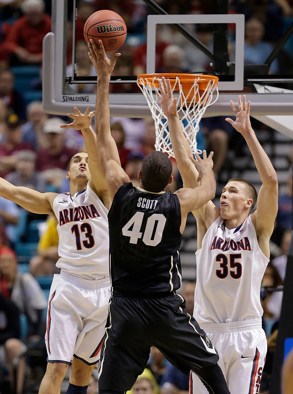 . Colorado\'s Josh Scott (40) shoots against Arizona\'s Nick Johnson (13) and Arizona\'s Kaleb Tarczewski (35) during the first half of an NCAA college basketball game in the semifinals of the Pac-12 Conference on Friday, March 14, 2014, in Las Vegas. (AP Photo/Julie Jacobson)