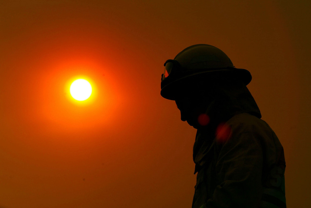 . SAN DIEGO - OCTOBER 27:  An exhausted firefighter from Marin County Fire Department is silhouetted against the smoke-shrouded sun near the Cedar Fire October 27, 2003 near Lakeside in San Diego, California. The death toll stands at 13, with more than 1,000 homes being reduced to ashes as southern California fires continue to burn. Winds have eased a bit, but 30,000 homes remain threatened by the fires, which have charred more than 400,000 acres, according to officials. Davis, who has activated the National Guard, predicted damages will be in the billions of dollars.  (Photo by Donald Miralle/Getty Images)