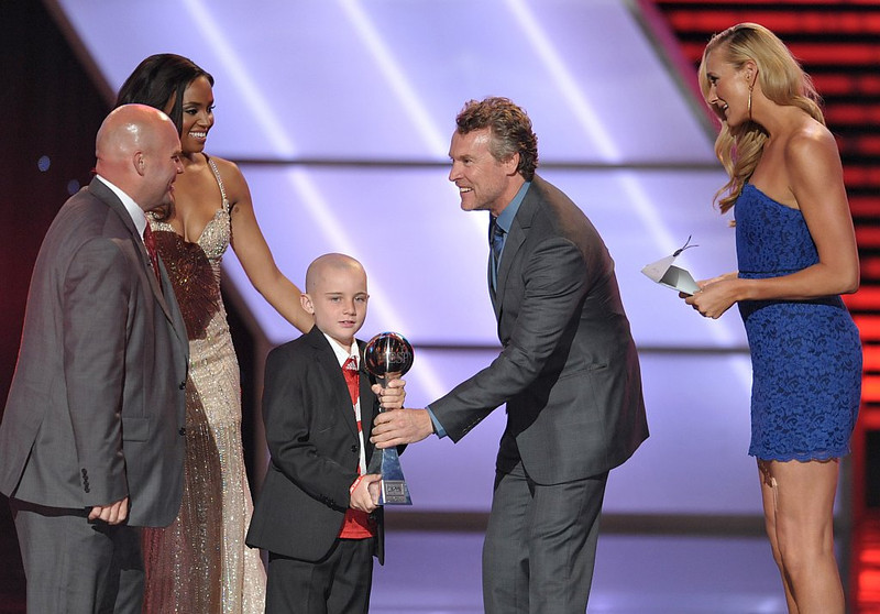 . From right, Kerri Walsh Jennings and Tate Donovan present the award for best moment to Jack Hoffman, center, at the ESPY Awards on Wednesday, July 17, 2013, at Nokia Theater in Los Angeles. At left is Andy Hoffman. (Photo by John Shearer/Invision/AP)