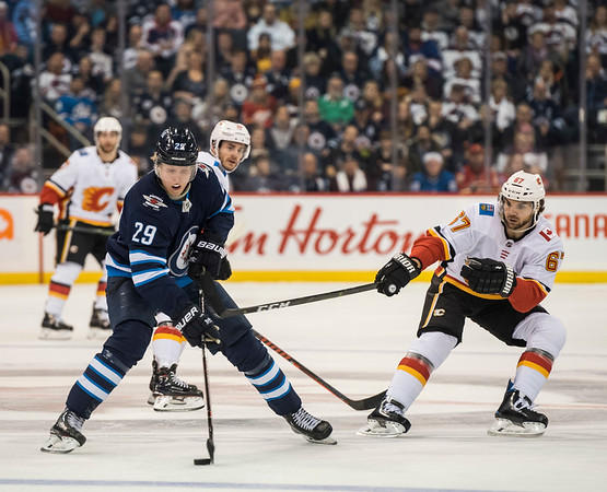DAVID LIPNOWSKI / WINNIPEG FREE PRESS  Winnipeg Jets #29 Patrik Laine looks to get a shot  past Calgary Flames #67 Michael Frolik Thursday December 27, 2018 at Bell MTS Place.