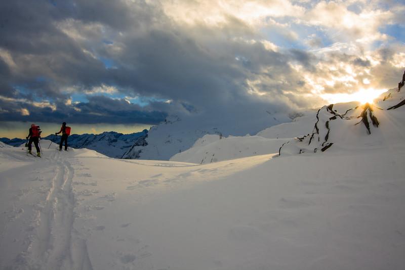 Skiers survey the wild afternoon skies below Capana Cristallina, Ticino, Swiss alps