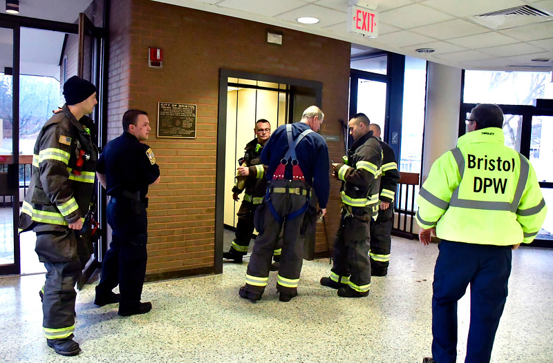 1/9/2019 Mike Orazzi | Staff Bristol firefighters while opening a stuck door on the elevator, where a man was stuck inside, at the Bristol Police Department Wednesday afternoon.