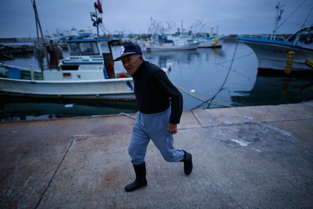 . 80-year-old fisherman Shohei Yaoita walks through Hisanohama port in Iwaki, about 30 km (19 miles) south of the Fukushima Daiichi nuclear power plant, Fukushima prefecture May 26, 2013. Commercial fishing has been banned near the tsunami-crippled nuclear complex since the March 2011 tsunami and earthquake. The only fishing that still takes place is for contamination research, and is carried out by small-scale fishermen contracted by the government.  Picture taken May 26, 2013. REUTERS/Issei Kato