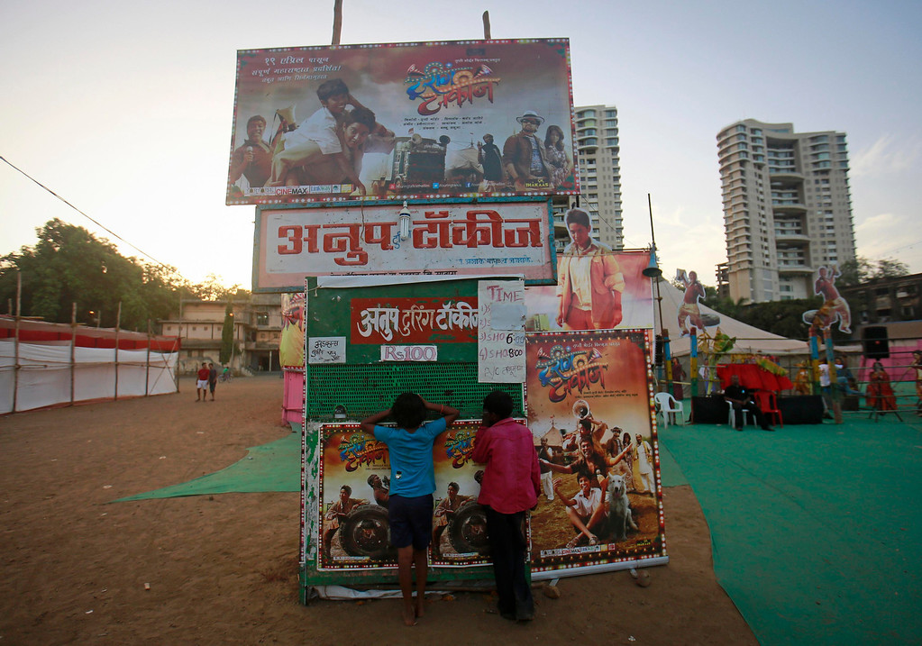 """. Boys inquire about tickets from a mobile ticket booth at Anoop Touring Talkies, a travelling tent cinema company in Mumbai April 23, 2013. Indian cinema marks 100 years since Dhundiraj Govind Phalke\'s black-and-white silent film \""""Raja Harishchandra\"""" (King Harishchandra) held audiences spellbound at its first public screening on May 3, 1913, in Mumbai. Indian cinema, with its subset of Bollywood for Hindi-language films, is now a billion-dollar industry that makes more than a thousand films a year in several languages. It is worth 112.4 billion rupees (over $2 billion) and leads the world in terms of films produced and tickets sold. Picture taken April 23, 2013. REUTERS/Danish Siddiqui"""