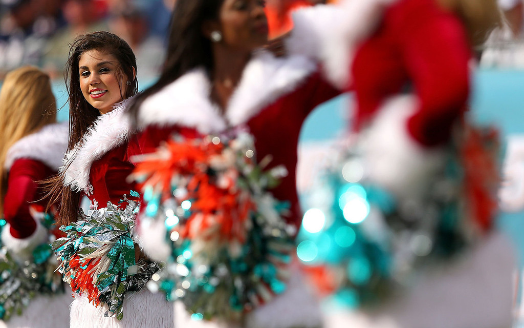 . A Miami Dolphins cheerleader looks on during a game against the New England Patriots at Sun Life Stadium on December 15, 2013 in Miami Gardens, Florida.  (Photo by Mike Ehrmann/Getty Images)