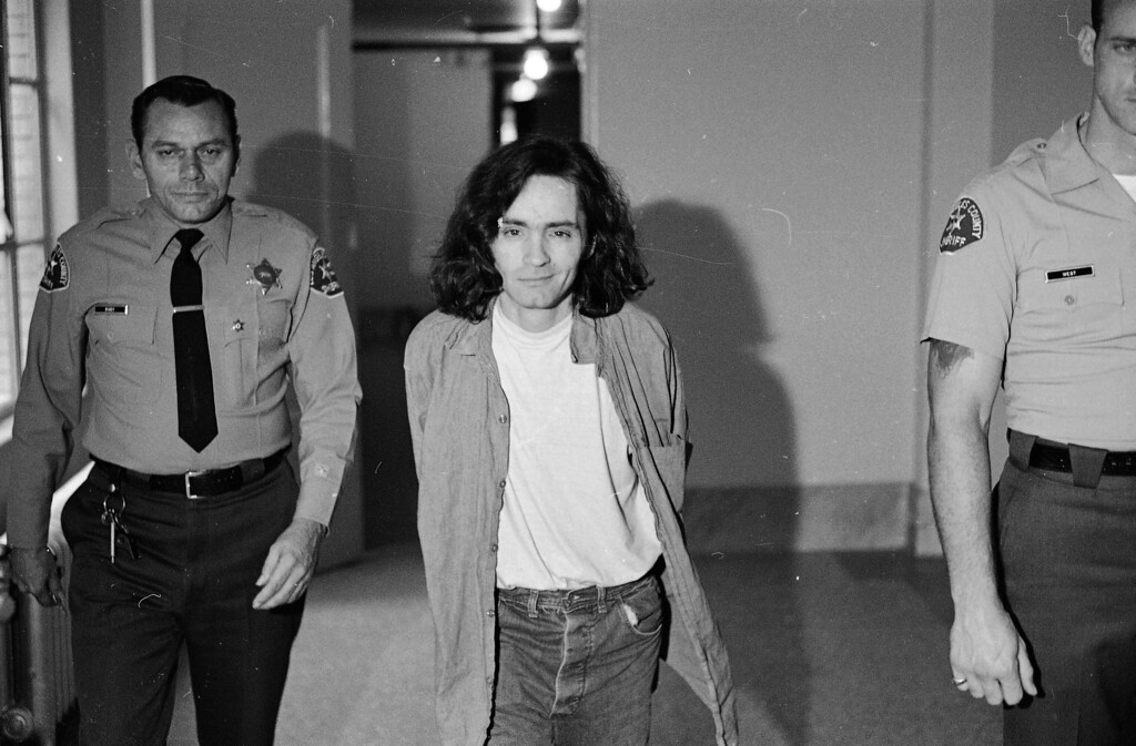 . Charles Manson is clean-shaven for the second time since his arrest, as he walks to the room where he listens to proceedings in his trial on murder charges in the Sharon Tate slayings, Oct. 21, 1970.  Manson and three women defendants in the case have been banished from the courtroom because of their misbehavior.  (AP Photo/George Brich)
