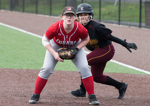 04/29/19 Wesley Bunnell | Staff New Britain softball defeated Conard at Chesley Park on Monday afternoon. Amanda Jacobs peeks over the first baseman shoulder as the pitch crosses the plate.