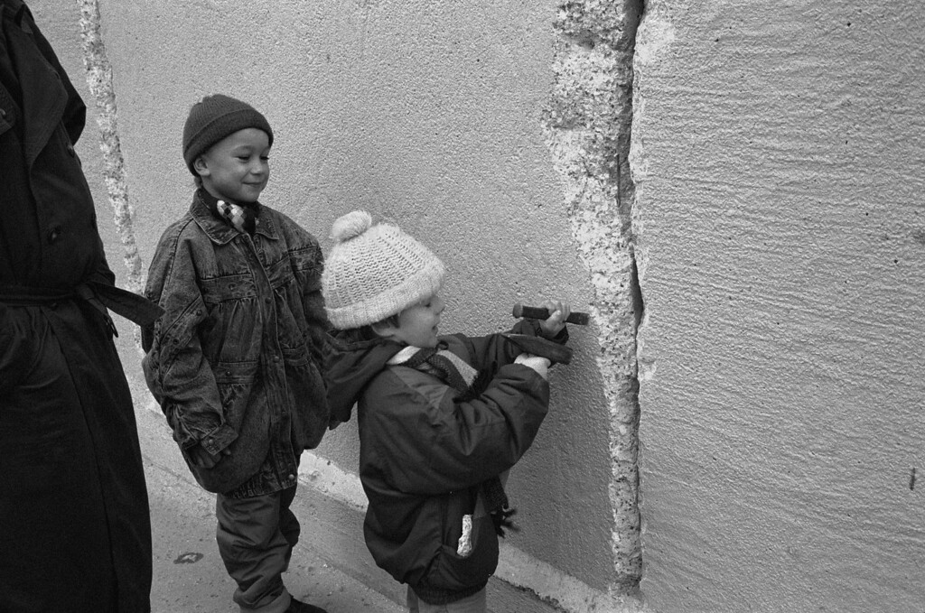 . An East German boy chips away at a section of the Berlin Wall at the effective end of the city\'s partition, 31st December 1989. (Photo by Steve Eason/Hulton Archive/Getty Images)