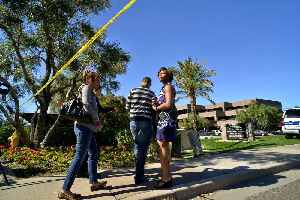 . People are escorted back into an office building by a police officer, second left, after a shooting at the building, background right, in Phoenix on Wednesday, Jan. 30, 2013. (AP Photo/Patrick Sison)