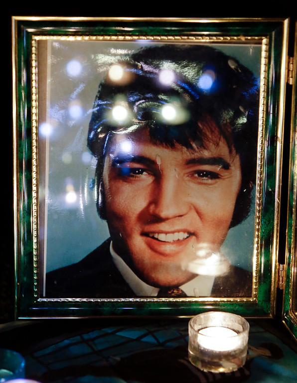 . FILE- This Aug. 15, 2012 photo shows candles reflected in a photo of Elvis Presley at a memorial set up by a fan at a candlelight vigil at Graceland, Presley\'s Memphis, Tenn. home. Friends and fans of late singer and actor Elvis Presley are descending on Memphis, Tennessee, for Elvis Week, the annual celebration of his life and career. It coincides with the 40th anniversary of the passing of Presley, who died on Aug. 16, 1977. (AP Photo/Mark Humphrey, File)